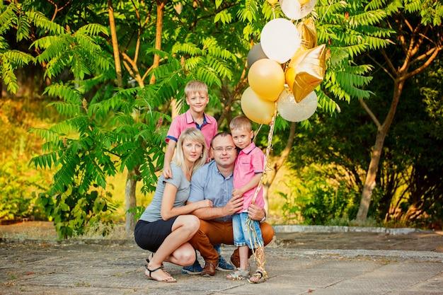 Glückliche familie mit den ballonen, welche die zeit im freien an einem sommertag verbringen.