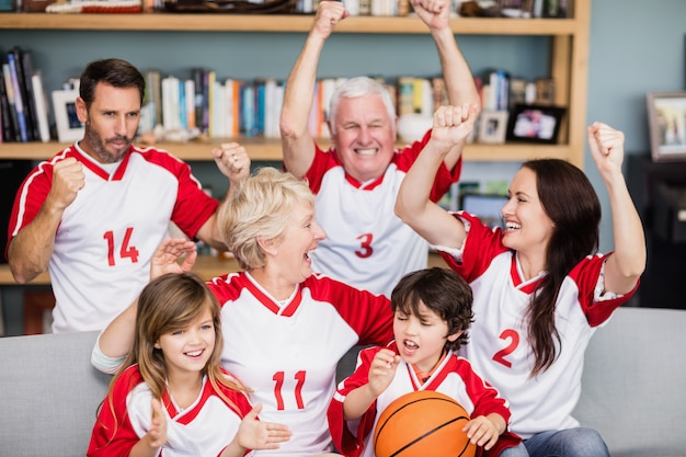 Glückliche familie mit den großeltern, die basketballspiel aufpassen