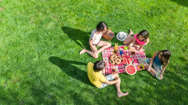 Glückliche familie mit den kindern, die picknick im park haben, eltern mit den kindern, die auf gartengras sitzen und draußen gesunde mahlzeiten essen