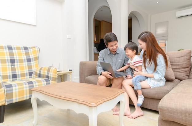 Glückliche familie mit den kleinkindern, die zusammen laptop genießen