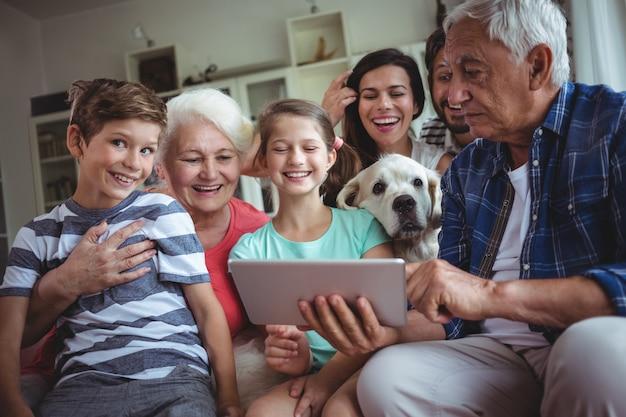 Glückliche familie mit digitaler tablette im wohnzimmer