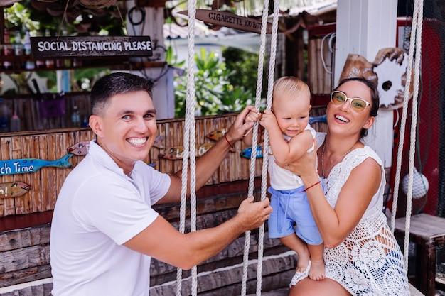 Glückliche familie mit einem jungen auf schaukel außerhalb des hotels