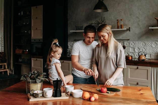 Glückliche familie mit einem kind kocht und lacht in der küche