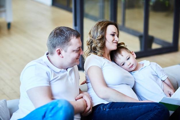 Glückliche familie mit einem kleinen sohn, der in einer gruppe auf dem sofa im wohnzimmer sitzt