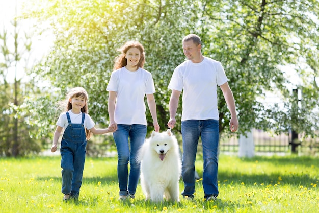 Glückliche familie mit einem weißen hund in einem sommerpark.