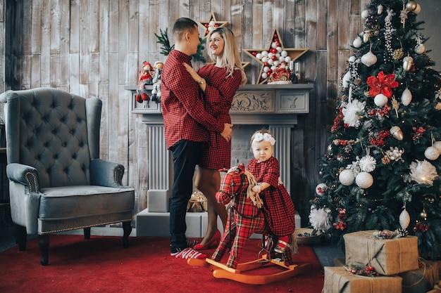 Glückliche familie mit einer kleinen tochter am neujahrs- oder weihnachtstag