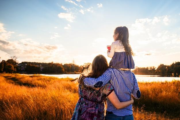 Glückliche familie mit einer kleinen tochter in einem feld in der natur, nach vorne schauend, blick von hinten, in den strahlen des sonnenuntergangs.