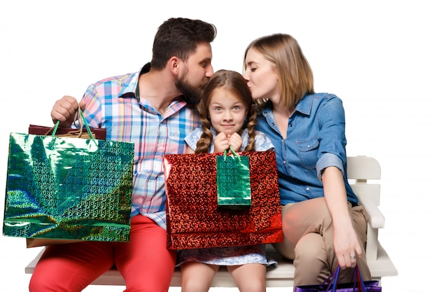 Glückliche familie mit einkaufstüten sitzen