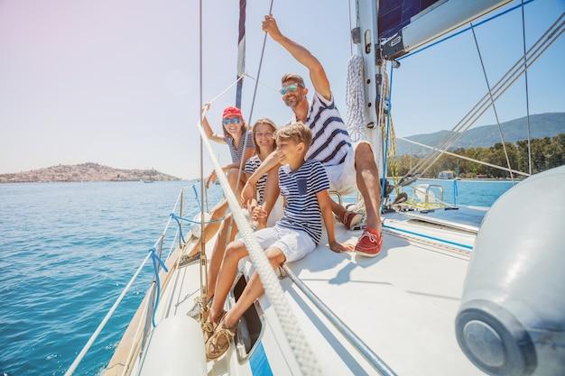 Glückliche familie mit entzückender tochter und sohn, die auf einer großen yacht ruhen