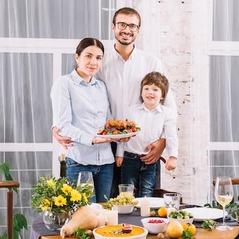 Glückliche familie mit gebackenem huhn bei tisch
