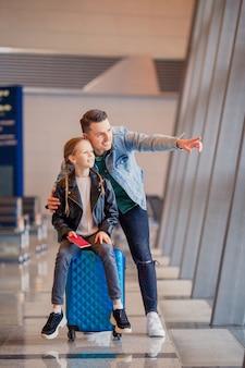Glückliche familie mit gepäck und bordkarte am flughafen, die auf das einsteigen wartet