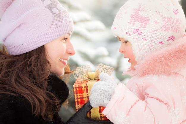 Glückliche familie mit geschenkbox im winter im freien. weihnachtsferienkonzept