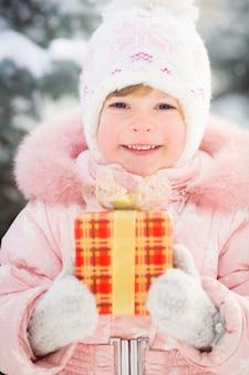 Glückliche familie mit geschenkbox im winter im freien