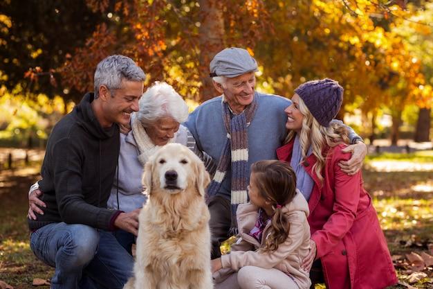 Glückliche familie mit hund am park während des herbstes