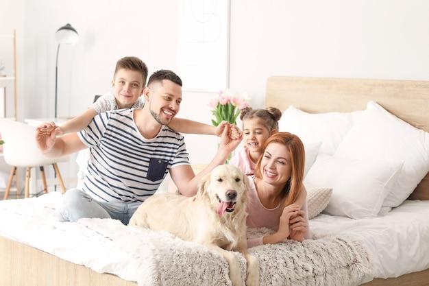 Glückliche familie mit hund im schlafzimmer zu hause