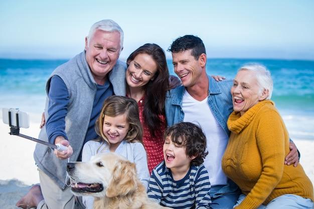 Glückliche familie mit ihrem hund, der ein selfie nimmt
