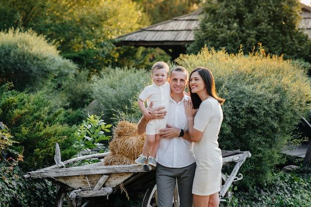 Glückliche familie mit ihrem sohn, der im park bei sonnenuntergang geht. glück. liebe