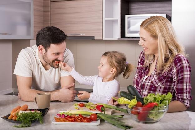 Glückliche familie mit ihrer kleinen tochter, die in der küche einen frischen salat mit gemüse macht