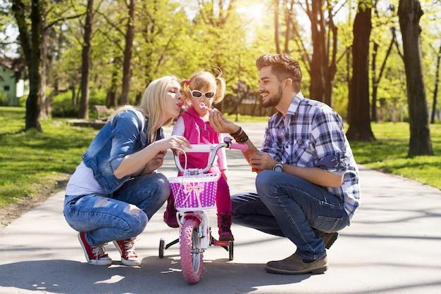 Glückliche familie mit jungen kaukasischen eltern, die ihrer tochter beibringen, wie man fahrrad fährt