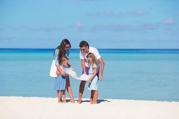 Glückliche familie mit karte am strand