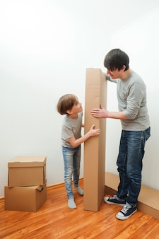Glückliche familie mit kartons im neuen haus am umzugstag. umzugstag und immobilienkonzept. träume werden wahr.