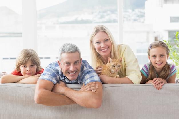 Glückliche familie mit katze auf sofa zu hause
