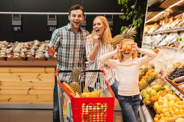 Glückliche familie mit kaufendem lebensmittel des kindes am gemischtwarenladen