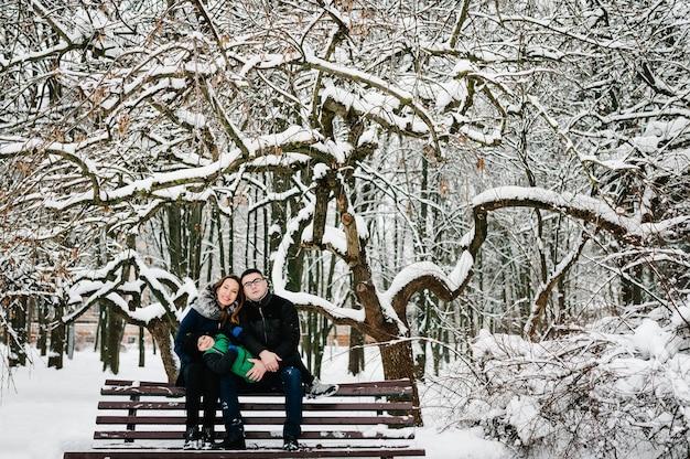 Glückliche familie mit kind in der winterkleidung, die draußen im park geht.