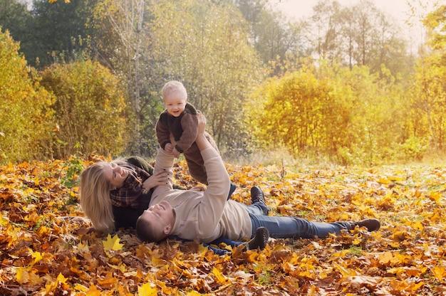 Glückliche familie mit kleinem baby im herbstpark