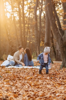 Glückliche familie mit kleinem nettem kind im park auf gelbem blatt mit großem kürbis im herbst
