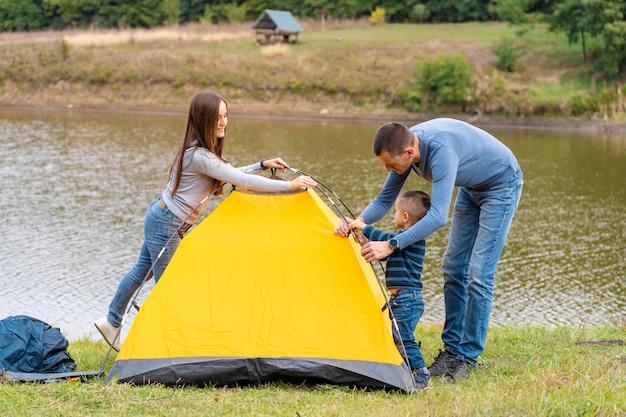 Glückliche familie mit kleinem sohn stellte campingzelt auf. glückliche kindheit, campingausflug mit den eltern. ein kind hilft beim aufbau eines zeltes