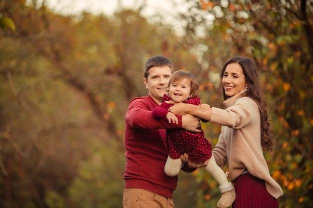 Glückliche familie mit kleiner tochter, die spaß auf einem spaziergang im park hat