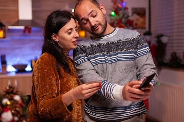 Glückliche familie mit kreditkarte, die online-shopping-geschenk bezahlt
