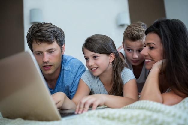 Glückliche familie mit laptop im schlafzimmer