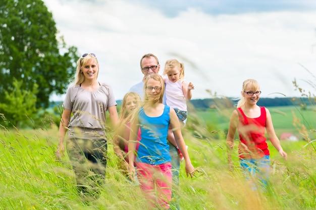 Glückliche familie mit mädchen oder töchtern, die im sommer auf einer wiese gehen