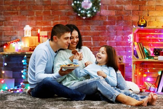 Glückliche familie mit milch und keksen im dekorierten weihnachtszimmer