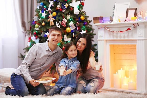 Glückliche familie mit milch und süßen keksen im dekorierten weihnachtszimmer