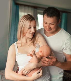 Glückliche familie mit neugeborenem baby, das in ihrer wohnung steht.