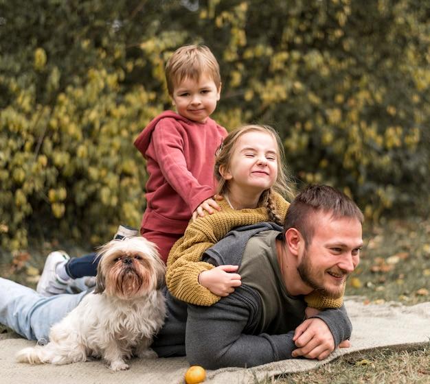 Glückliche familie mit niedlichem hund draußen