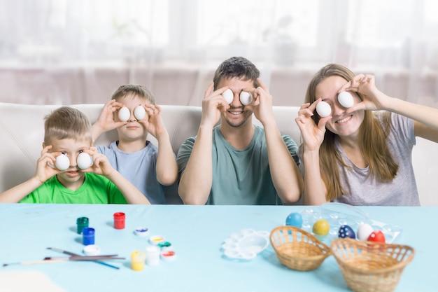 Glückliche familie mit ostereiern. mama, papa und zwei söhne halten eier statt augen und lächeln. auf dem tisch liegen pinsel und farben. glückliche familie, die sich auf ostern vorbereitet.