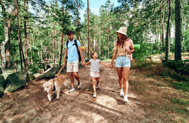 Glückliche familie mit rucksäcken und labrador-hundewanderungen im wald. camping, reisen, wandern.