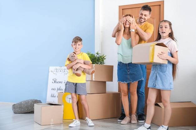 Glückliche familie mit sachen in ihrem neuen haus