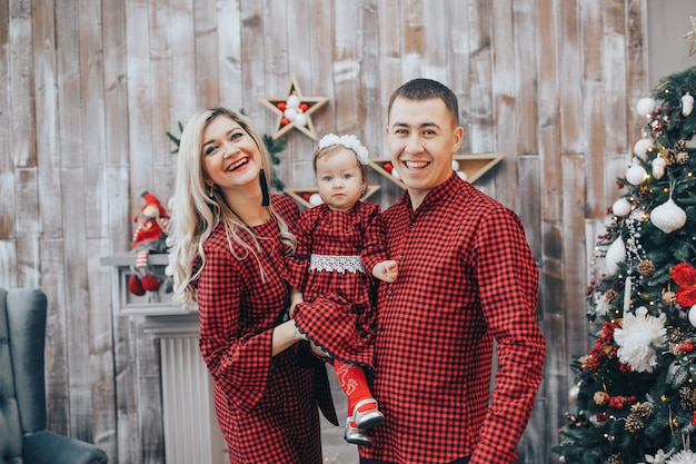Glückliche familie mit seiner kleinen tochter zusammen in dekoriertem raum