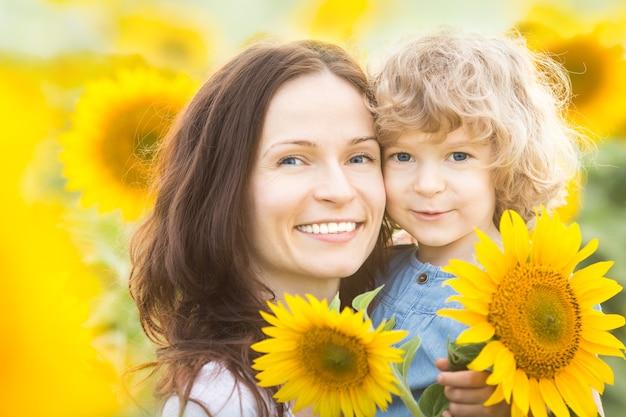 Glückliche familie mit sonnenblumen, die sich im frühlingsfeld im freien amüsieren