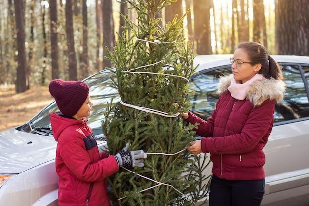 Glückliche familie mit weihnachtsbaum, der nahe dem auto steht