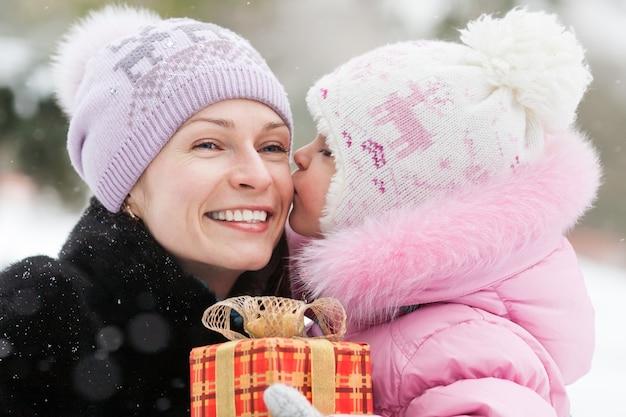 Glückliche familie mit weihnachtsgeschenkbox im winterpark