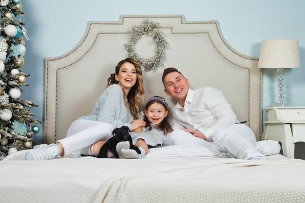 Glückliche familie mit weihnachtsgeschenken auf dem boden zu hause an frohe weihnachten und ein glückliches neues jahr. familie mit hund, der spaß in der nähe des weihnachtsbaums im schlafzimmer auf dem bett hat. schöne eltern geben der tochter einen hund. platz kopieren