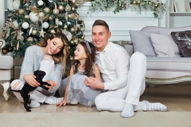 Glückliche familie mit weihnachtsgeschenken auf dem boden zu hause an frohe weihnachten und ein glückliches neues jahr. familie mit hund, der spaß nahe weihnachtsbaum im wohnzimmer hat schöne eltern geben der tochter einen hund. platz kopieren
