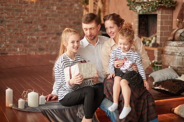 Glückliche familie mit weihnachtsgeschenken, die in einem gemütlichen wohnzimmer sitzen.