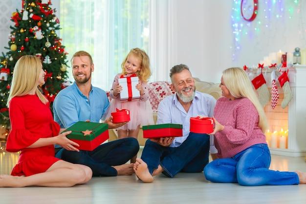 Glückliche familie mit weihnachtsgeschenken zu hause